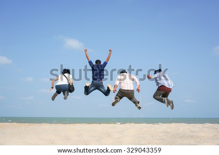 Young friends having fun on the beach and jumping against a backdrop of a blue skies. Seen in the picture, motion blur on the feet because of acrobatic movements - stock photo
