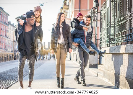 Young friends having fun outdoors - Five students outdoors, men carrying two girls on piggyback - stock photo