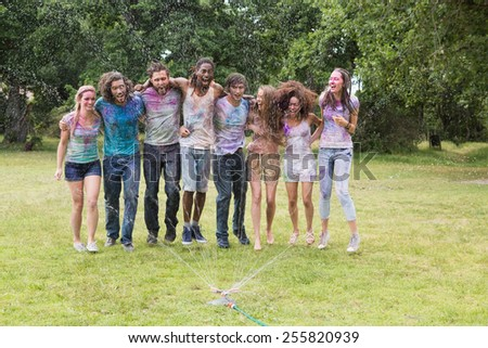 Young friends having fun with powder paint on a sunny day - stock photo