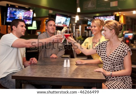 Young friends  in a modern bar and lounge toasting. - stock photo