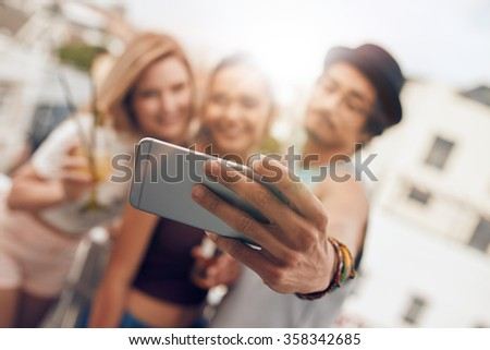 Young friends in a party taking self portrait with their smart phone. Focus on mobile phone in man's hand. - stock photo