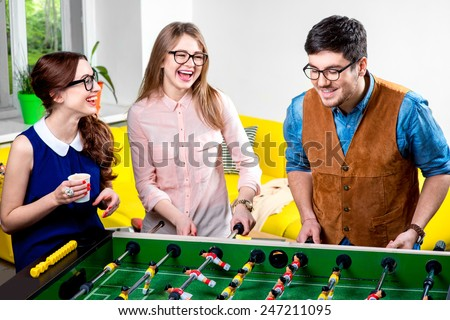 Young friends or students having fun together playing table football - stock photo