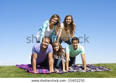 Young Friends Playing Outdoors making a human pyramid - stock photo