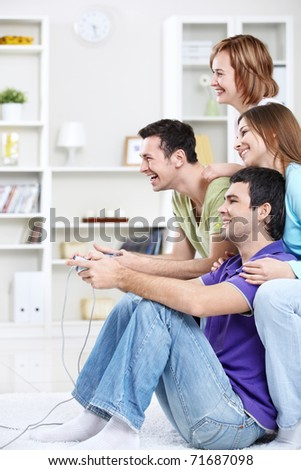 Young friends playing video games at home - stock photo