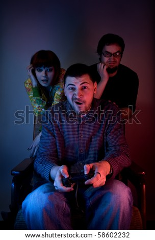 Young friends playing video games in front of tv or computer