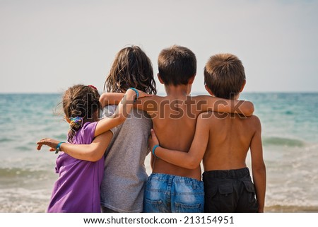Young friends portrait at the beach looking at the sea. - stock photo