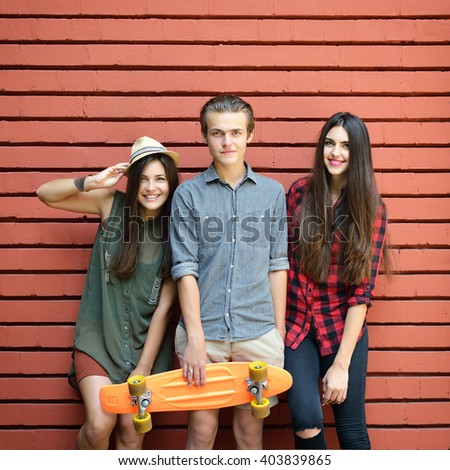 Young friends posing with penny board summer outdoor against red brick wall. Urban lifestyle, happiness, joy, friends, teenage, first love concept. Image toned and noise added. - stock photo