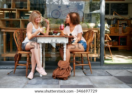 Young friends sitting at coffee shop drinking mocktails. Young women meeting at sidewalk table having refreshing drinks. - stock photo
