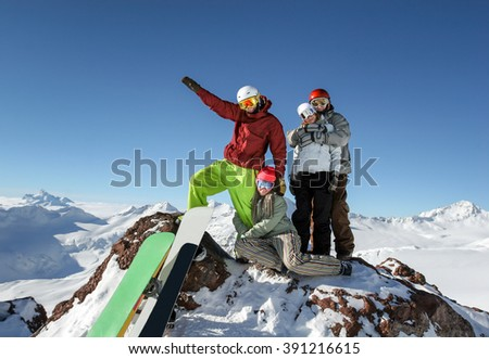 Young friends snowboarders standing together on the top of the slope on a background of mountains and blue sky