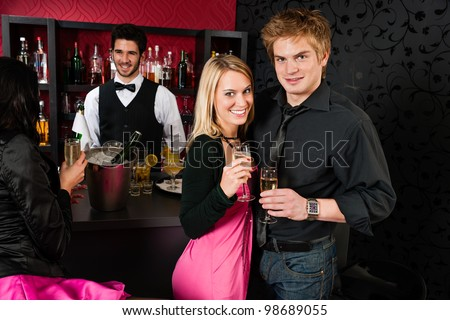 Young friends toasting with champagne in front of the bar - stock photo