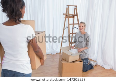 Young friends unpacking moving boxes in their new home - stock photo