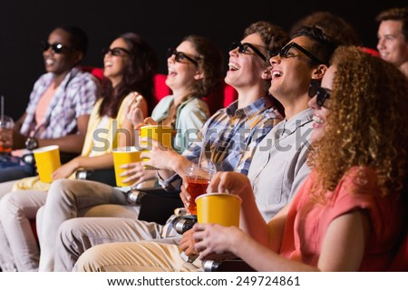 Young friends watching a 3d film at the cinema - stock photo