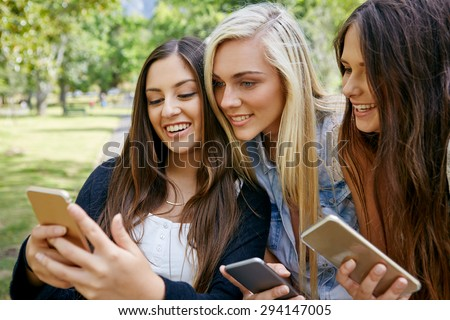 young friends watching viral social media video on mobile cell phone outdoors - stock photo