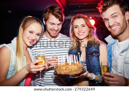Young friends with champagne and cake looking at camera at birthday party