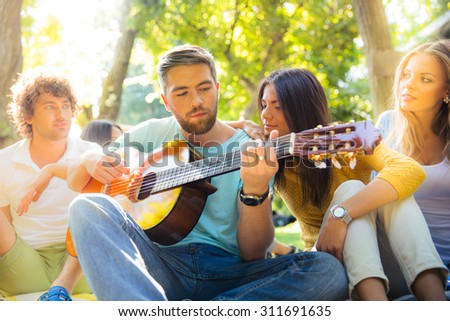 Young friends with guitar having fun outdoors - stock photo