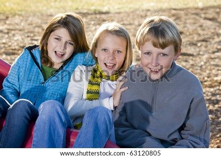 Young friends (10-11 years) sitting together at bottom of slide on playground