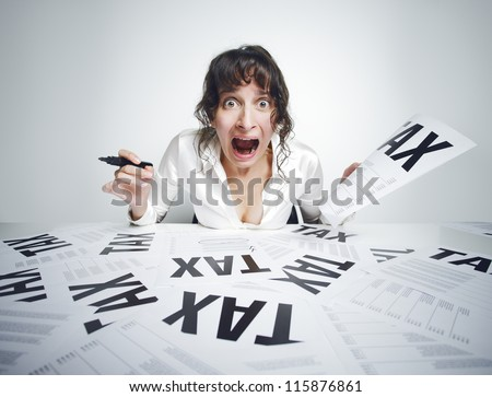 Young frightened woman shouting out while sitting at her paperwork-covered desk  with a marker in one hand and a tax bill in the other one - stock photo