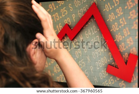 Young frustrated broker lady watching a monitor showing a graph that describes stock market crash (crisis concept). Selective focus.  - stock photo