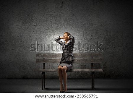 Young frustrated businesswoman covering ears with hands and screaming - stock photo