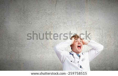 Young frustrated crazy doctor screaming very emotionally - stock photo