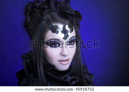 Young ftylish woman in black dress with artistic visage with smokey-eyes