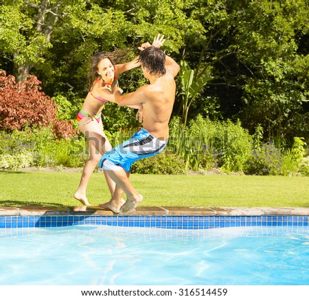 Young fun couple jumping into a tropical swimming pool - stock photo