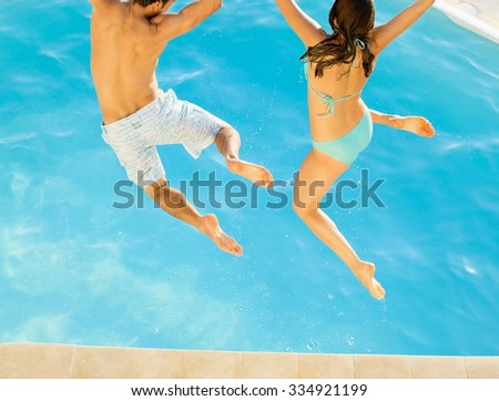 Young fun couple jumping into a tropical swimming pool