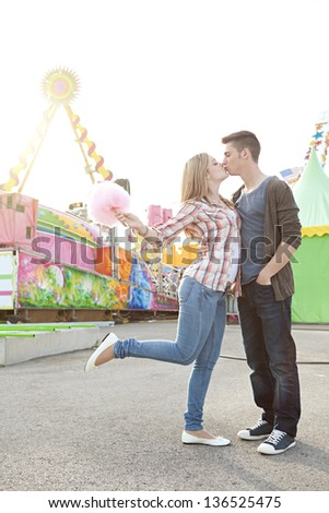 Young fun couple kissing and holding cotton candy floss sweet while visiting an amusement park during a sunny day. - stock photo