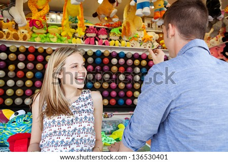 Young fun couple playing darts games in an amusement park arcade during a sunny day, with toys and prices around them, smiling. - stock photo