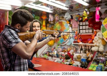 Young fun couple playing shooting games at amusement park - stock photo