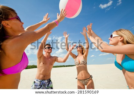 Young fun people are playing ball on the beach - stock photo