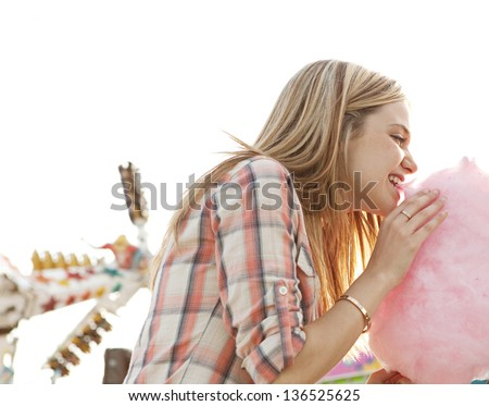 Young fun teenager girl biting into a cotton candy floss sweet while visiting an amusement park during a sunny day. - stock photo
