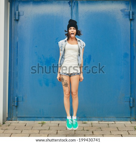 Young funky woman jumping and having fun. Lifestyle portrait of girl - stock photo