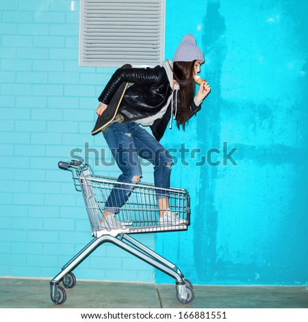 Young funky woman with ice cream and skateboard standing in shopping cart over blue brick wall. Naughty girl having fun . Indoors, lifestyle - stock photo