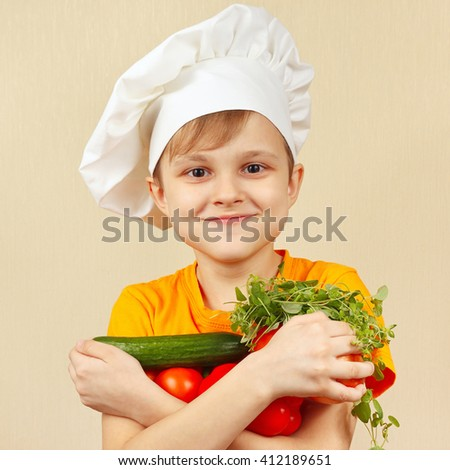 Young funny chef with the fresh vegetables - stock photo