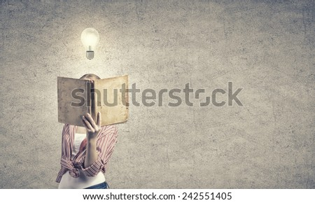 Young funny girl with opened book in hands - stock photo