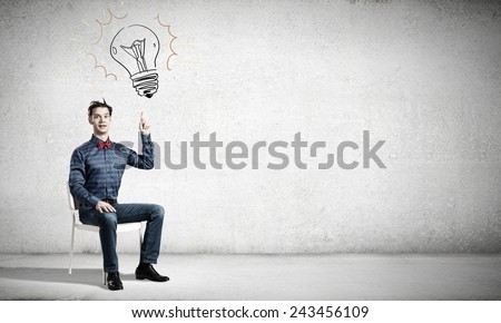 Young funny guy sitting in chair and pointing upwards - stock photo