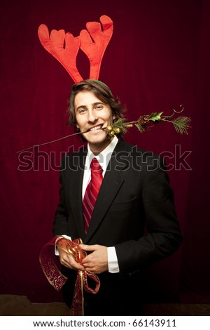 young funny guy with christmas decorations on red velvet background - stock photo
