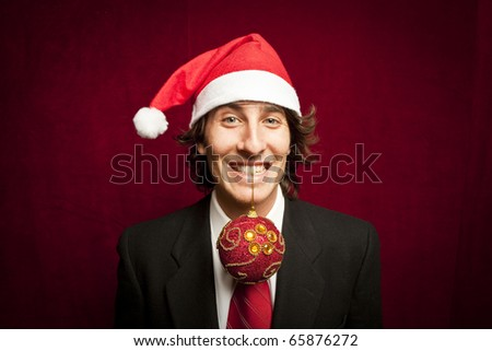 young funny guy with christmas hat on red velvet background