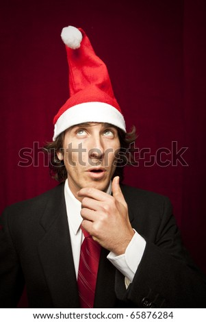 young funny guy with christmas hat on red velvet background - stock photo