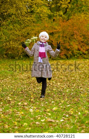 young funny little cute girl havng fun in autumn park standing with lifted hands