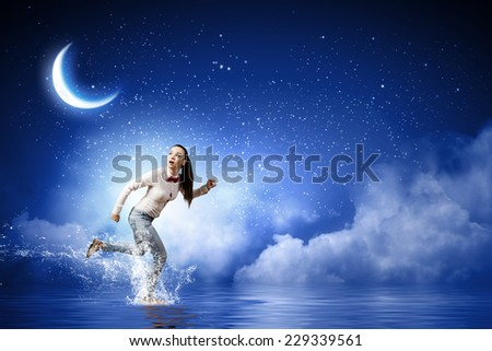 Young funny pretty woman in jeans running in a hurry - stock photo