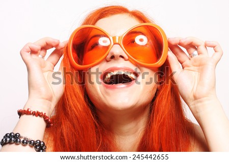 Young funny redhair woman in big orange glasses - stock photo