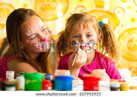 Young funny sisters playing with painting - stock photo