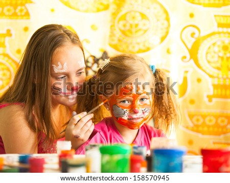 Young funny sisters playing with painting. - stock photo