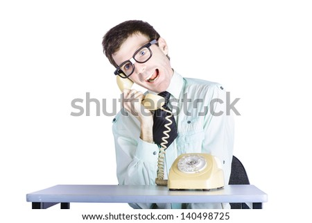 Young funny telemarketing businessman sitting at table with retro telephone, annoying call center clerk concept, white background - stock photo