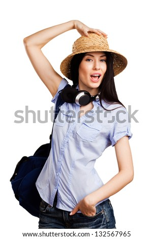 Young funny woman in a hat with a backpack and headphones on white background
