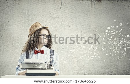 Young funny woman in glasses using typewriter - stock photo