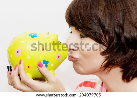 Young funny woman in profile and decorative ceramic piggy bank. - stock photo