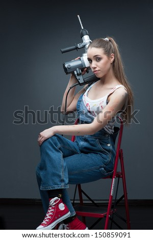 young funny woman standing at ladder and holding puncher